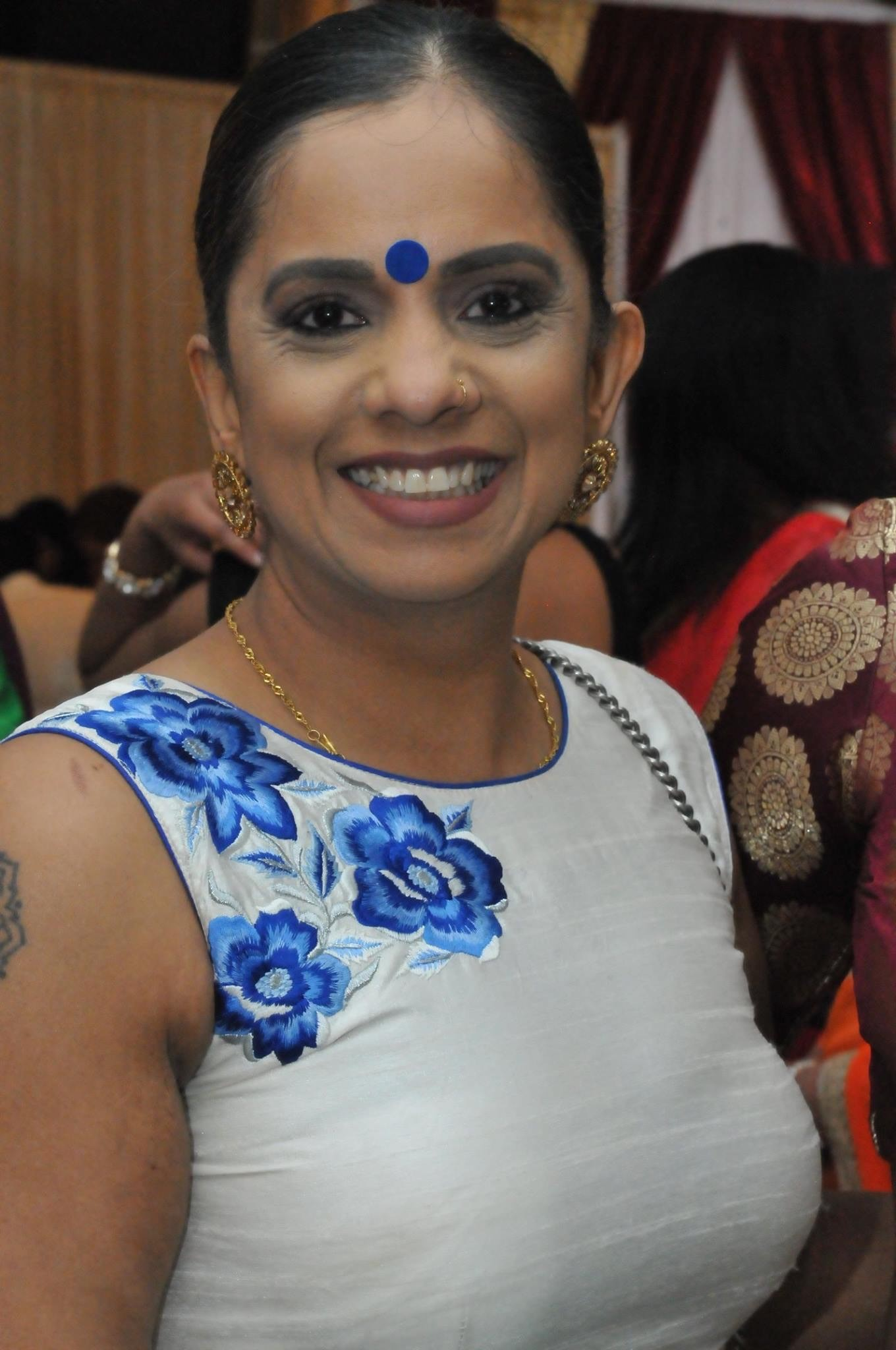 Missing person Nirla Sharma is shown smiling wearing a blue dress and gold jewlery. She has brown eyes, brown hair, and a medium complexion.